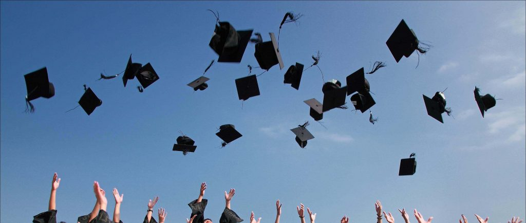 generic image of hats being thrown in the air for a graduation celebration